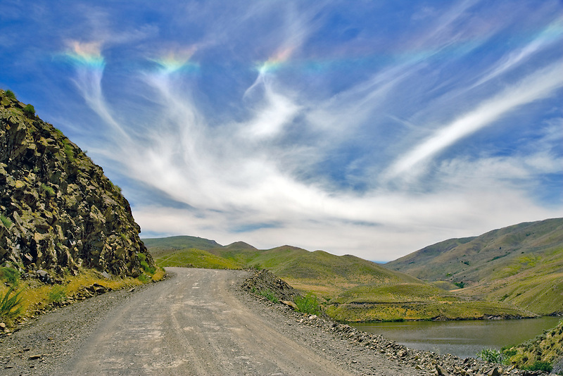 Sun Dog in sky with dirt road over Hell's Canyon National Recreational Area, Oregon