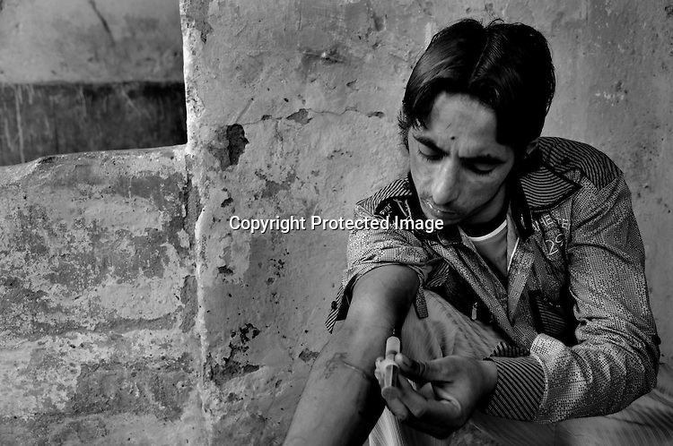 Wakil Singh is a drug addict from Tilak Vihar, Delhi. His father died in the 1984 Sikh Genocide in India. Wakil was only 5 months then. His father was a government employee. His mother got his father's job on compensatory grounds. After 10 years his mother too died of T.B. leaving him alone. In depression, Wakil started taking drugs along with other young boys of the locality. Today some of his old drug-addict friends are dead and even he knows that he also will be dead soon. Kind neighbours feed him everyday. Tilak Vihar in New Delhi is called the widow colony. Widows and children of the Sikhs who were killed in 1984 Sikh Genocide live here. Four thousand Sikhs were killed in 72 hours in Delhi alone but no body till date has been punished for such an inhuman crime. Illiteracy, drug addiction, child labour and immense poverty characterize the area. Twenty five years ago all the male family members above the age of 15 were killed and burnt, leaving their uneducated widows and children behind to suffer, even after 25 years. The present generation is jobless, steeped in alcoholism and have lost their directions in life. November 2009. New Delhi, India, Arindam Mukherjee