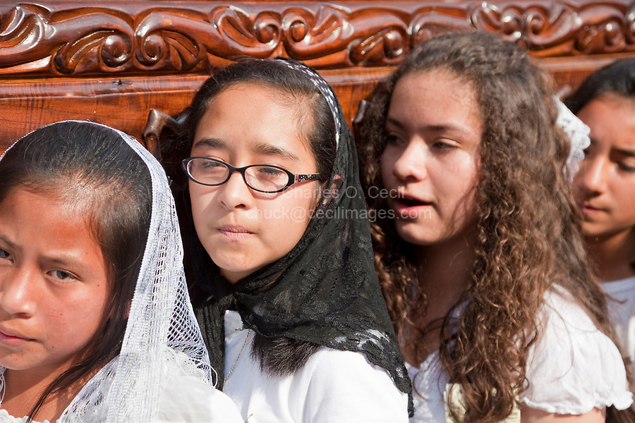Antigua, Guatemala.  Semana Santa (Holy Week).  Young Girls Carry an Anda (Float) in a Religious Procession.