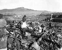 1945-09-24 - Battered religious figures stand watch on a hill above a tattered valley. Nagasaki, Japan. September 24, 1945, 6 weeks after the city was destroyed by the world's second atomic bomb attack. Photo by Cpl. Lynn P. Walker, Jr. (Marine Corps) NARA FILE #: 127-N-136176<br /> Français : Statues religieuses fracturées sur une colline au dessus d'une vallée entièrement détruite. Nagasaki, Japon, 24 septembre 1945, 6 semaines après la destruction de la ville par le deuxième bombardement atomique de l'histoire.
