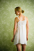 Blonde woman wearing a negligee standing in front of floral wallpaper