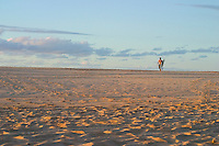 Man in distance walks along the beach carrying surfboard.