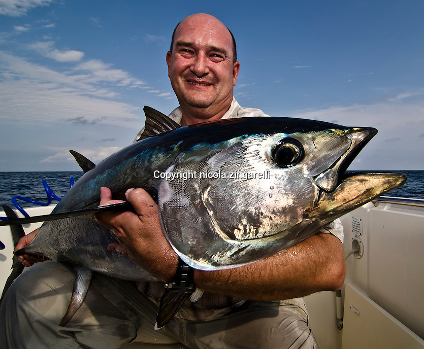A spanish fisherman in his late 40s holding a Bluefin Tuna (Thunnus thynnus) caught in the Delta of the Ebro river, Mediterranean sea