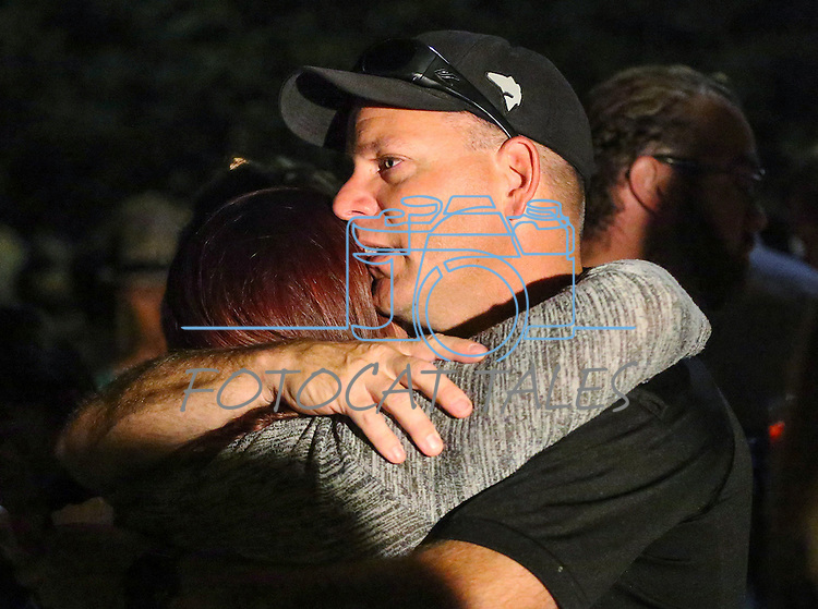 Carson City Sheriff's Deputy Don Gibson hugs the widow of a deputy killed in the line of duty early Saturday morning. Hundreds of residents and law enforcement came out to show their support for the family and the department at a candlelight vigil in Carson City, Nev., on Saturday, Aug. 15, 2015. <br /> Photo by Cathleen Allison