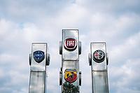 Torino 04-05-2020 <br /> Fiat FCA logos at the entrance of the Fiat Chrysler Automobiles factory. <br /> In compliance with the safety regulations due to the Coronavirus Covid-19 pandemic, body temperature is measured using thermoscanners and pistol thermometers besides the mandatory use of protective masks . <br /> Today, May 4, the second phase of the measures taken by the Italian government against the coronavirus pandemic began. <br /> <br /> Loghi di Fiat, Lancia e Alfa Romeo all'ingresso dello stabilimento di FCA Fiat Mirafiori . In ottemperanza alle normative di sicurezza per la pandemia di Coronavirus Covid-19, viene misurata a tutti la temperatura corporea prima dell'ingresso in fabbrica, mediante termoscanner e termometri a pistola oltre all'uso obbligatorio delle mascherine protettive.<br /> Oggi è iniziata la fase due (2) delle misure contro la pandemia di coronavirus adottate dal governo italiano. <br /> Photo: Federico Tardito / Insidefoto