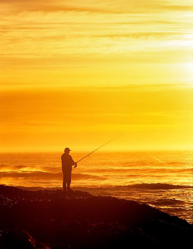 Fisherman on rocky shore of Cape Perpetua. Oregon.