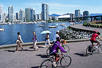 Vancouver, BC, British Columbia, Canada - City Skyline at False Creek, People cycling and walking on Seawall, Summer