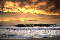 Scenic sunrise over ocean with dramatic clouds.