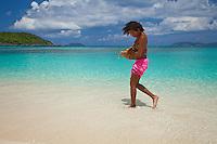 Young woman at the beach with a basket of local fruit<br /> Hawksnest Beach<br /> Virgin Islands National Park<br /> St. John, U.S. Virgin Islands