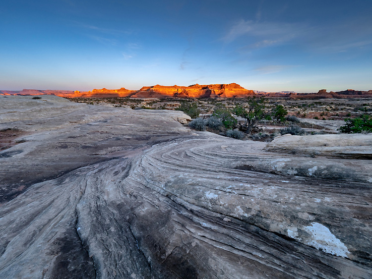 Rock formations in the Needles District of Canyonlands National Park in Utah glow at sunset.