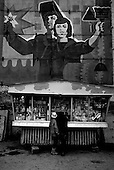 Norilsk, Russia  .May-June 1997.At a kiosk, which sells mostly western goods in the nickel mining city of Norilsk, two young girls are dwarfed by a massive emblem left over from the communist era..