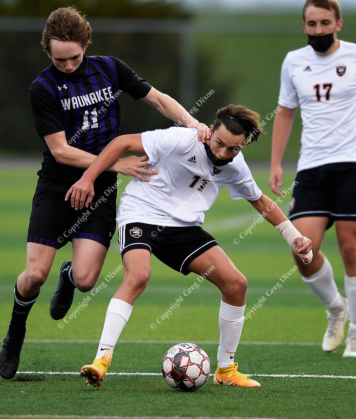 Oregon's Noah Malcook (center) fights for the ball against Waunakee's Lane Miller (left), as Oregon takes on Waunakee in Wisconsin WIAA Badger Conference boys high school soccer on Tuesday, Apr. 27, 2021 at Waunakee High School | Wisconsin State Journal article front page C1 and C8 Sports Apr. 28, 2021 and online at https://madison.com/wsj/sports/high-school/soccer/isaiah-jakels-late-goal-lifts-waunakee-past-oregon-in-boys-soccer/article_50476402-c4fa-5f08-a2f1-dfbf24dad5fd.html