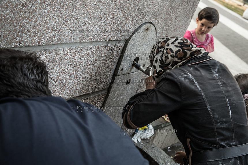 Migranti nel parco della stazione dei bus di Belgrado. Migrants on the bus station park in Belgrade Beograd<br /> Bambina osserva una donna che beve alla fontana  Little girl looks at a woman drinking at a fountain