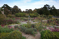 The walled garden is divided into square flowerbeds connected by paved paths