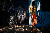 A Salvadoran sex worker stands in the shadow of a tree while waiting for clients in the street in San Salvador, El Salvador, 11 November 2016. Although prostitution is not legal in El Salvador, dozens of street sex workers, wearing provocative miniskirts, hang out in the dirty streets close to the capital's historic center. Sex workers of all ages are seen on the streets but a significant part of them are single mothers abandoned by their male partners. Due to the absence of state social programs, they often seek solutions to their economic problems in sex work. The environment of street sex business is strongly competitive and dangerous, closely tied to the criminal networks (street gangs) that demand extortion payments. Therefore, sex workers employ any tool at their disposal to struggle hard, either with their fellow workers, with violent clients or with gang members who operate in the harsh world of street prostitution.