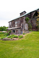 Pretty, large old barn set on top of a slope, with toolshed work building attached.