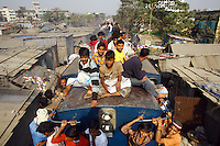 Passnegers cling to the sides and sit on the roof of a train. In Bangladesh many people ride on the roofs of trains as frequently that is the only space available. For others, the fares are too high and can be avoided or reduced by travelling on the roof. However, the riding on roofs and other parts of train exteriors leads to regular accidents, many of them fatal..