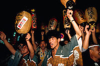 Excited Japanese celebrants cheer and wave lanterns during the Kawagoe matsuri (festival) evening street festival. Kawagoe, Saitama prefecture, Japan.