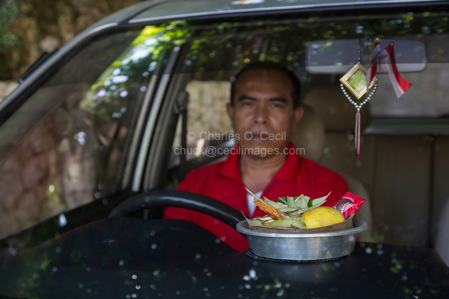 Bali, Indonesia.  A Canang, a Balinese Offering to the Gods, on the Dashboard of a Private Car.  Protective Talisman Hanging on the Rear-view Mirror.
