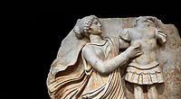 Close up of a Roman Sebasteion relief  sculpture of a Goddess inscribing a trophy, Aphrodisias Museum, Aphrodisias, Turkey.   Against a black background.<br /> <br /> A draped goddess strides forward to inscribe a military trophy to which is bound a kneeling female captive. The goddess is probably a personification such as Honour, Virtue or Courage.