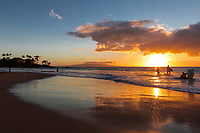 A family enjoys the waters of Wailea Beach, Maui, at sunset.