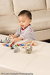 16 month old toddler boy playing with toy people human figures and toy animals vertical