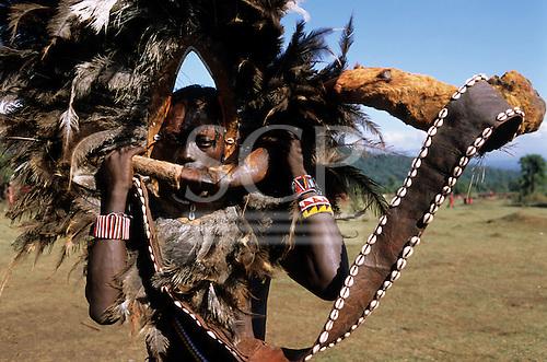 Lolgorian, Kenya. Siria Maasai Manyatta; moran 'lion head' with horn musical instrument.