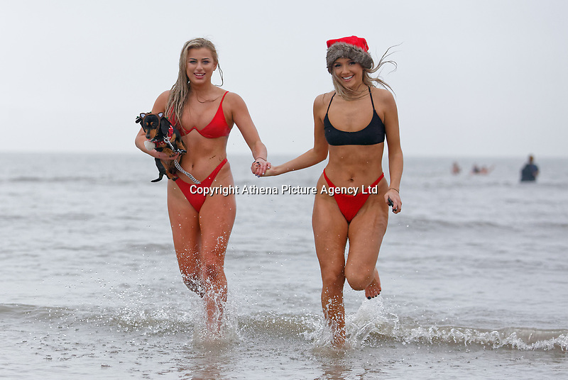 Pictured: Two young women in bikinis and Santa hats run in the sea.  Tuesday 25 December 2018<br /> Re: Hundreds of people take part in this year's Porthcawl Christmas Swim in south Wales, UK.