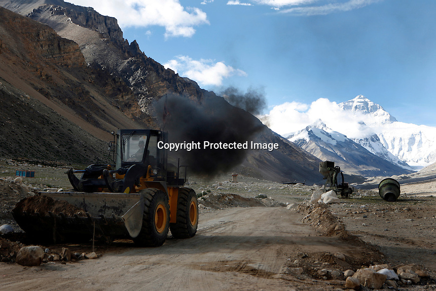 """China started building a controversial 67-mile """"paved highway fenced with undulating guardrails"""" to Mount Qomolangma, known in the west as Mount Everest, to help facilitate next year's Olympic Games torch relay./// A digger belches smoke as it clears the road in front of Rongbuk Monastery  on the road to Everest Base Camp.<br /> Tibet, China<br /> July, 2007"""
