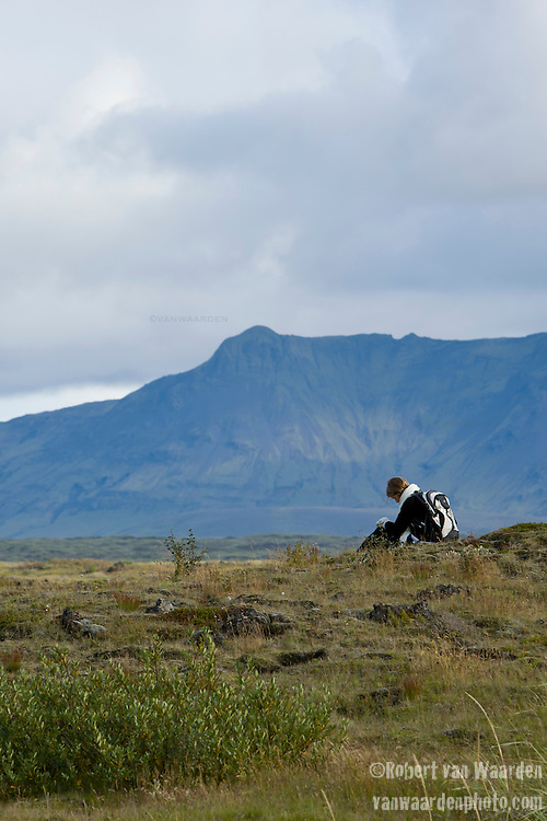 A young woman takes a moment to record some thoughts in the Iceland landscape. She is a member of the Cape Farewell Youth Expedition organized by the British Council of Canada.