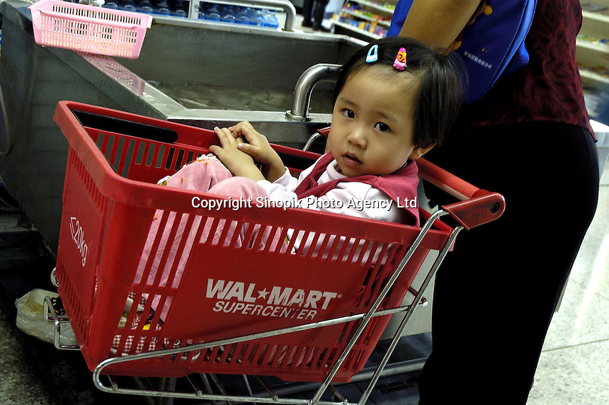 Inside US Wal Mart 'Supercenter' flagship store in China's richest city, Shenzhen, with customer's daughter sitting in a shopping basket..05 Nov 2004