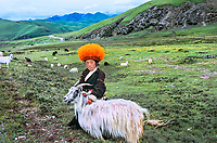 Child from orange hat tribe with goat, Kham, Tibet 2010