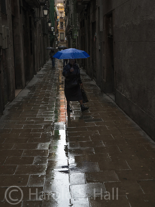 Life carries on in the narrow streets of Barcelona in the rain.