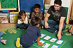 Education preschool 3-4 year olds children choosing play time activities from chart after circle time with assistance of young male teacher