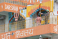 India, Rishikesh.  Bells Mark the Entrance to two Shrines in the Tera Manzil Temple.  Shiva's Trident also present.
