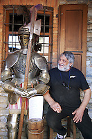 """Switzerland. Canton Ticino. Novaggio. The Vinera mill is located on the """"Sentiero delle Meraviglie"""" which is a walking path. Sergio Ghezzi, dressed in black pants and tee-shirt, is the owner of the Vinera Mill. While seating close to an old suit of a knight's armor, he smokes a cigerette and laughs.The """"Sentiero delle Meraviglie"""" is a guided trail which is plunged into nature, but every so often signs of human activity appear. Novaggio is located in the Malcantone area. 16.03.2010 © 2010 Didier Ruef"""
