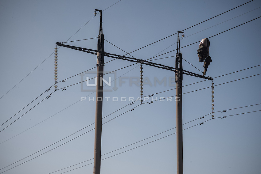 Dead Ukrainian soldier thrown by the explosion on the high-voltage wires