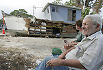 Seventy-two year old Loys Calvin Cheney (no relation to the VP) (R) sits in the shade of a pine tree with his caretaker Pamely Kay Shaver in Eastpoint.  The pair sit in the shade in the day time to stay cool and then retire to their home (background) aboard a 40 foot commercial boat that was heavily damaged and pushed into the roadway by Hurricane Dennis.  FEMA came by and filled out a report on the loss of his full time residence and yesterday his doctor made a house call at the pine tree to check on his feet which are in bad shape because of his diabetes.