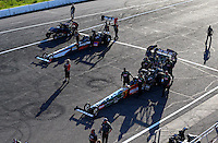 Aug 15, 2014; Brainerd, MN, USA; Crew members for the teams of NHRA top fuel dragster driver Terry McMillen (bottom) and Clay Millican in the staging lanes during qualifying for the Lucas Oil Nationals at Brainerd International Raceway. Mandatory Credit: Mark J. Rebilas-