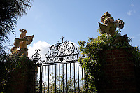 Two carved, fantastical beasts guard a wrought-iron gateway in the garden