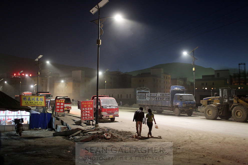 People walk down a street at night the town of Yushu on the Tibetan Plateau, in western China.
