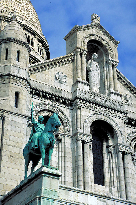 Sacre Coeur Basilica part of facade, base of dome and equestrian statue from southwest. Paris, France.