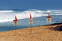 Signs warn people to stay out of the dangerous surf that pounds the North Shore of Oahu each winter. Hawaii.