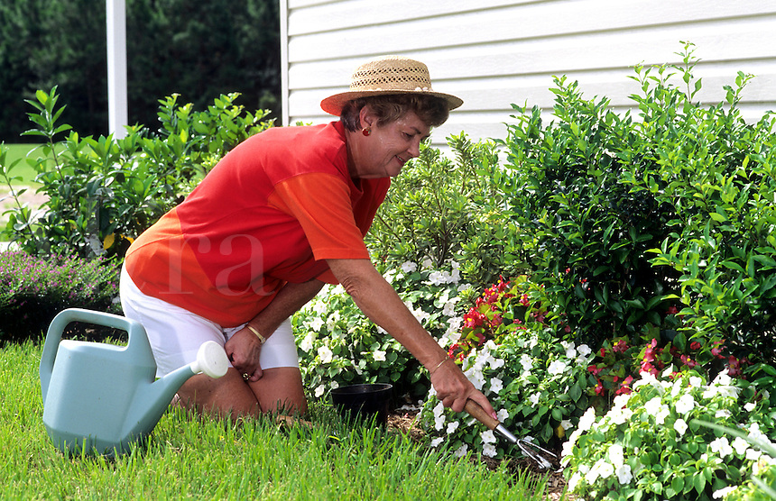 Retired elderly woman enjoying working in the garden.