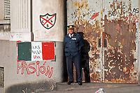 A police man standing guard in front of a solid rusty old iron door in uniform and with a cap pulled down over his eyes leaning against a wall with graffiti, one word spelling Pasion, passion Montevideo, Uruguay, South America