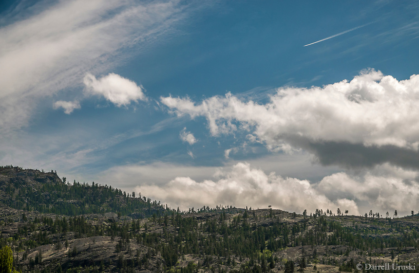 Landscape photograph of a high flying jet airplane flying over the mountain tops in the Okanagan Valley in British Columbia, Canada.