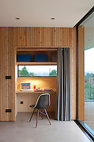 A home office is created in a curtained alcove in a corner of the living area