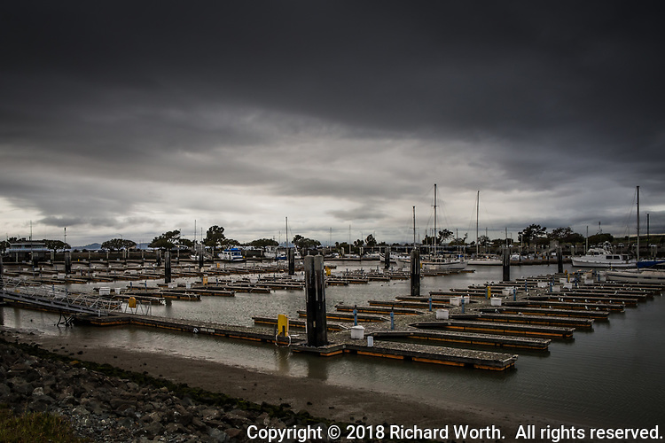 Under stormy skies, empty boat slips, one after another after another, at the San Leandro Marina on the eastern shores of San Francisco Bay.