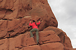 Woman scrambling up rock face in Arches National Park, Moab, Utah, USA. .  John offers private photo tours in Arches National Park and throughout Utah and Colorado. Year-round.
