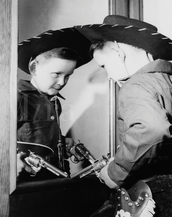 Young boy in cowboy suit pondering his image in mirror.  1950's.